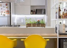 Yellow accents add brightness to the stylish and innovative kitchen