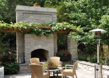 A simple pergola structure covered in vine offers ample shade for the outdoor living area