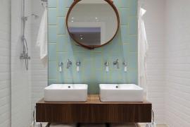 Aqua and yellow add subtle color to the stylish bathroom