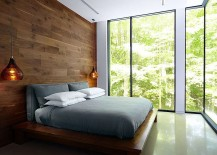 Bedroom with wooden accent wall and bedside pendant lighting