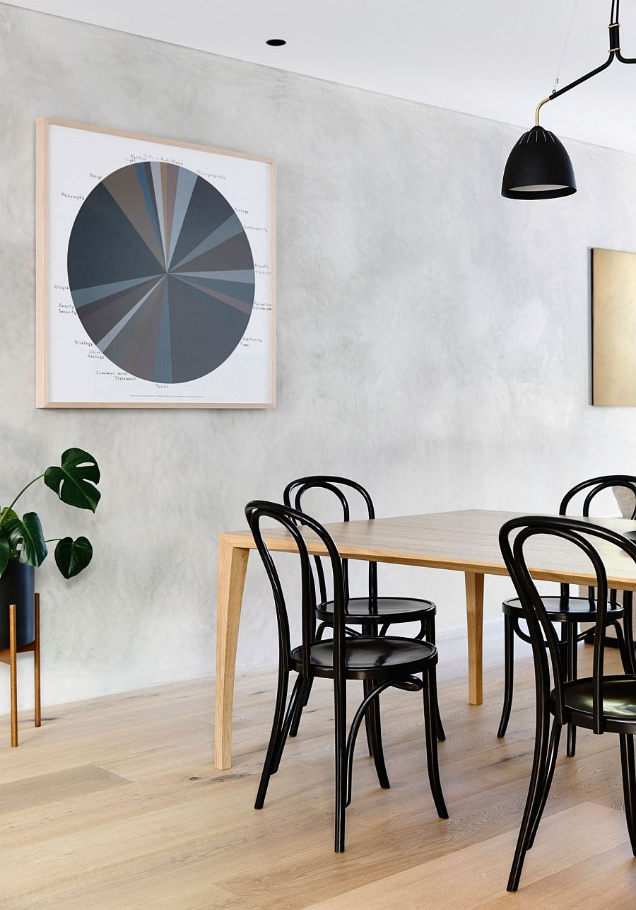 Black dining table chairs anchor the light-filled and cheerful dining room