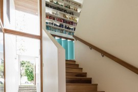 Bookshelf in the stairwell adds color to the contemporary interior