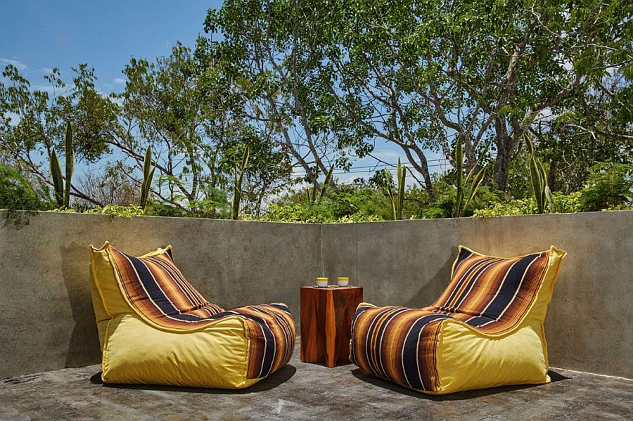 Bright yellow outdoor cushioned chairs with colorful stripes on a casual cement deck