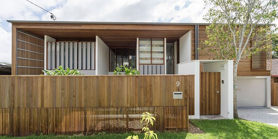 Broad and unique street facade of the Backyard House draped in wood