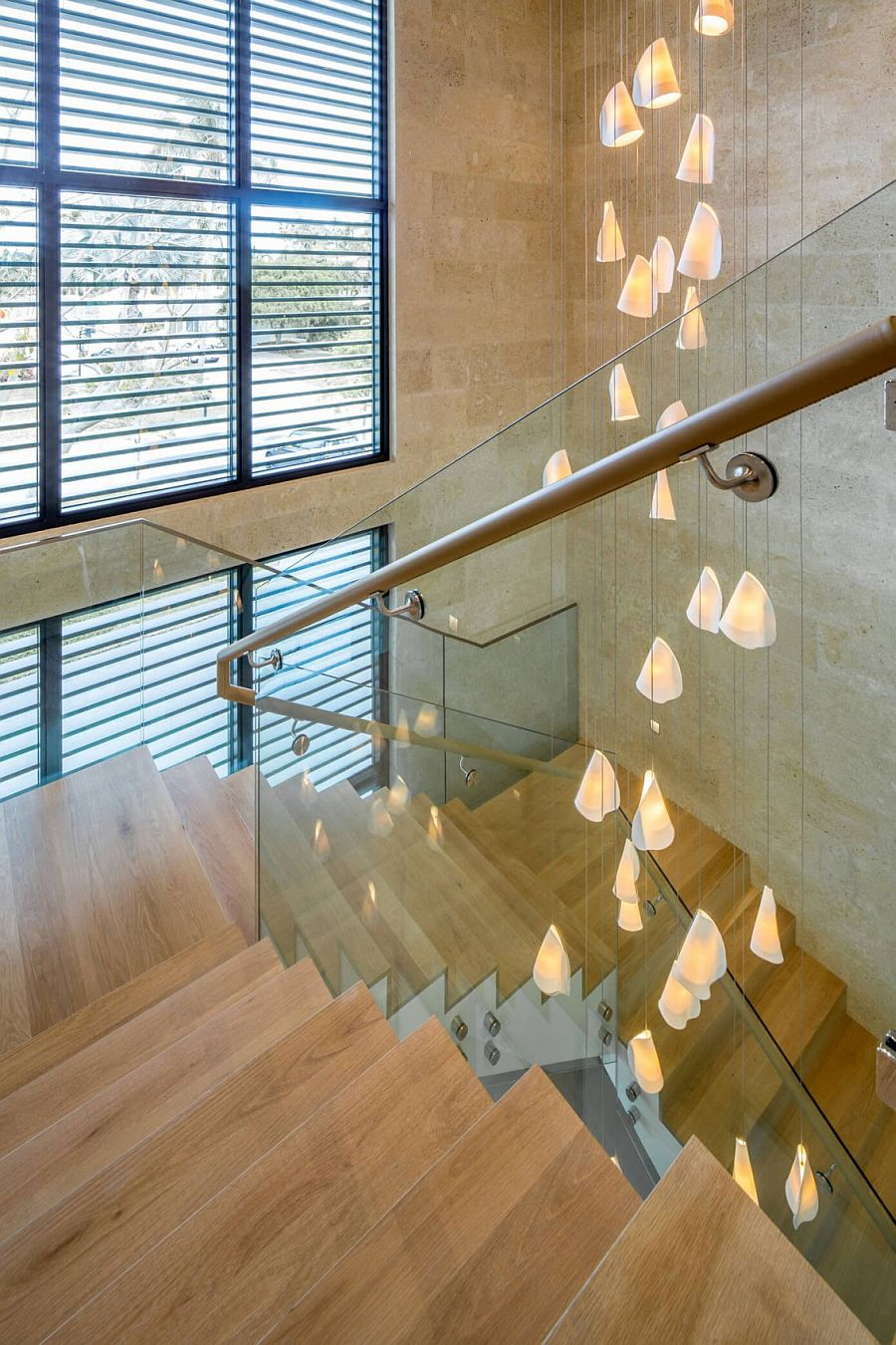 Cascading chandelier illuminates the contemporary stairwell