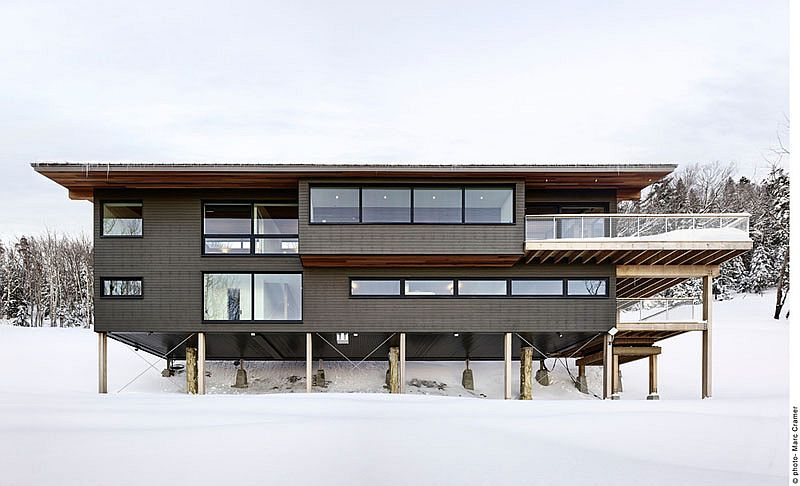 Chalet on cedar columns minimizes ecological footprint Contemporary Weekend Ski Chalet Designed for Fun Family Time