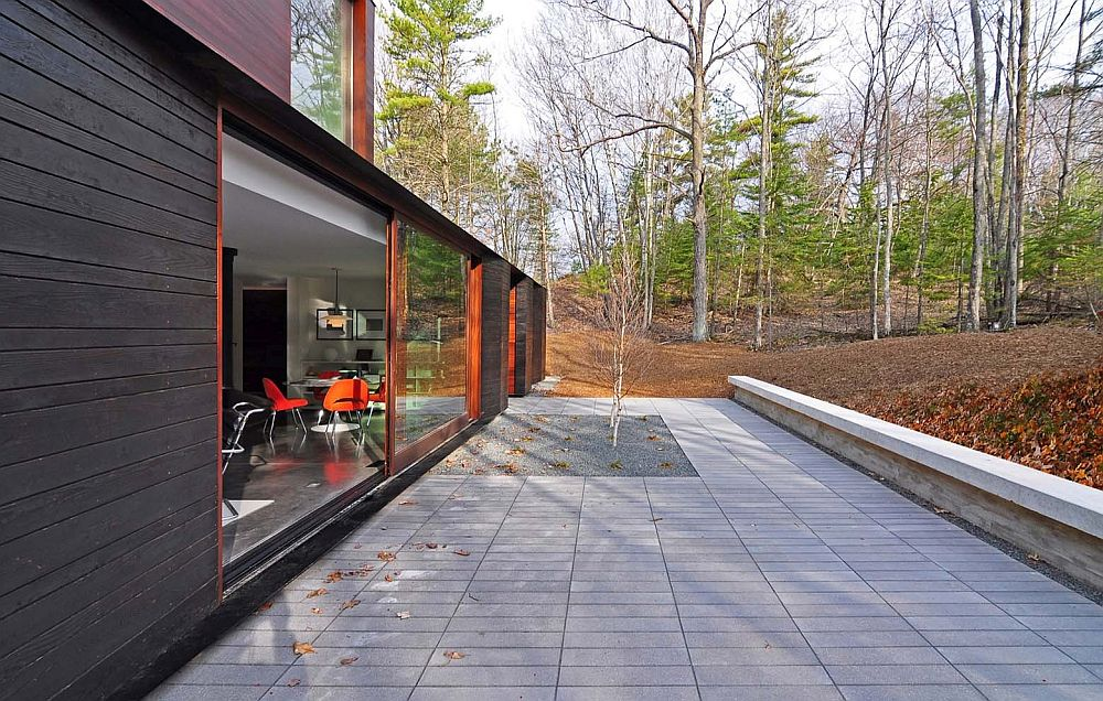 Concrete patio around the beautiful forest house with sliding glass doors