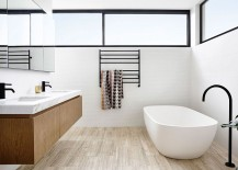 Contemporary-bathroom-with-penny-tiles-on-the-wall-freestanding-bathtub-and-floating-wooden-vanity-217x155