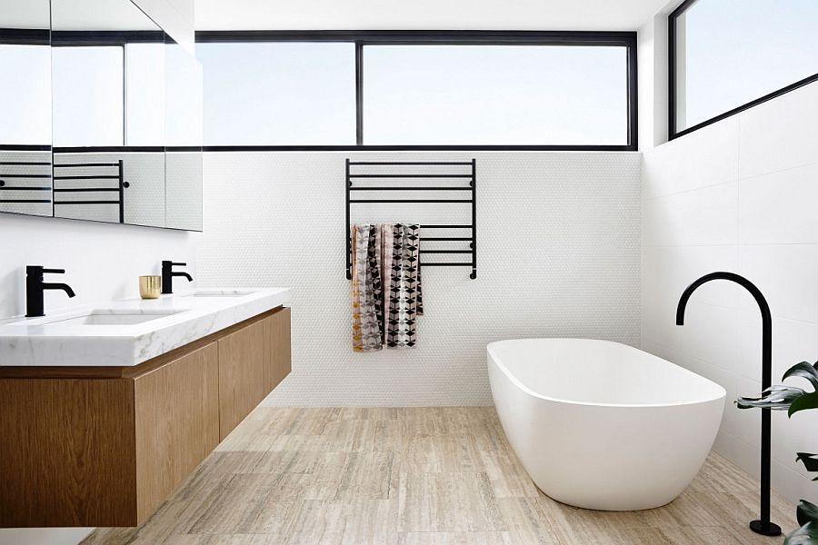 Contemporary bathroom with penny tiles on the wall, freestanding bathtub and floating wooden vanity