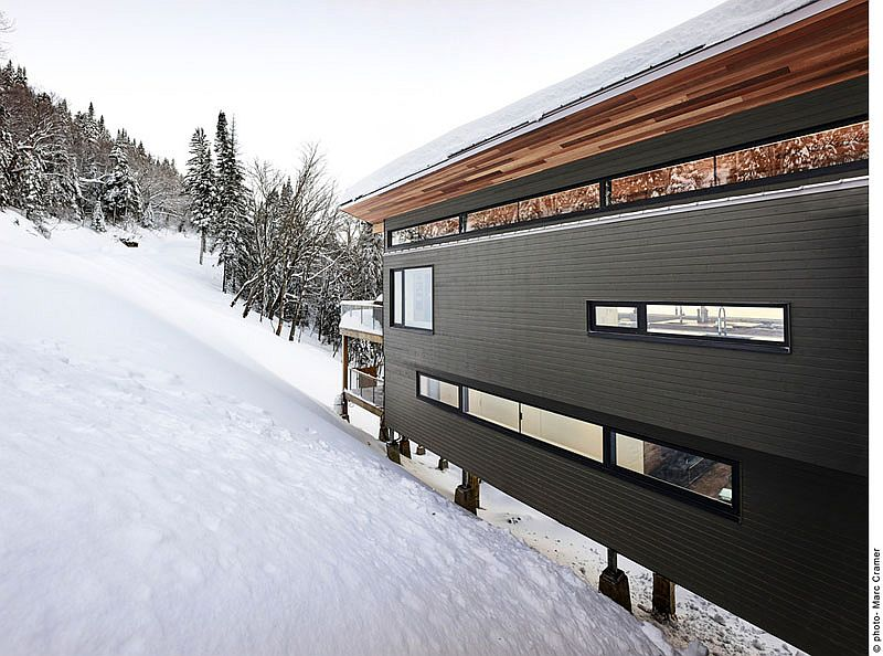 Contemporary chalet in Quebec with dark stained white cedar siding