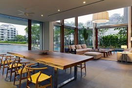 Contemporary dining room of Sentosa Cove home with a view of the canal and live edge dining table