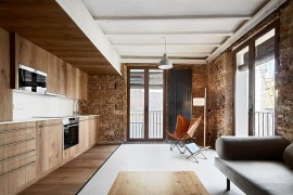 Contemporary ergonomics are coupled with original exposed brick walls and tiles surfaces
