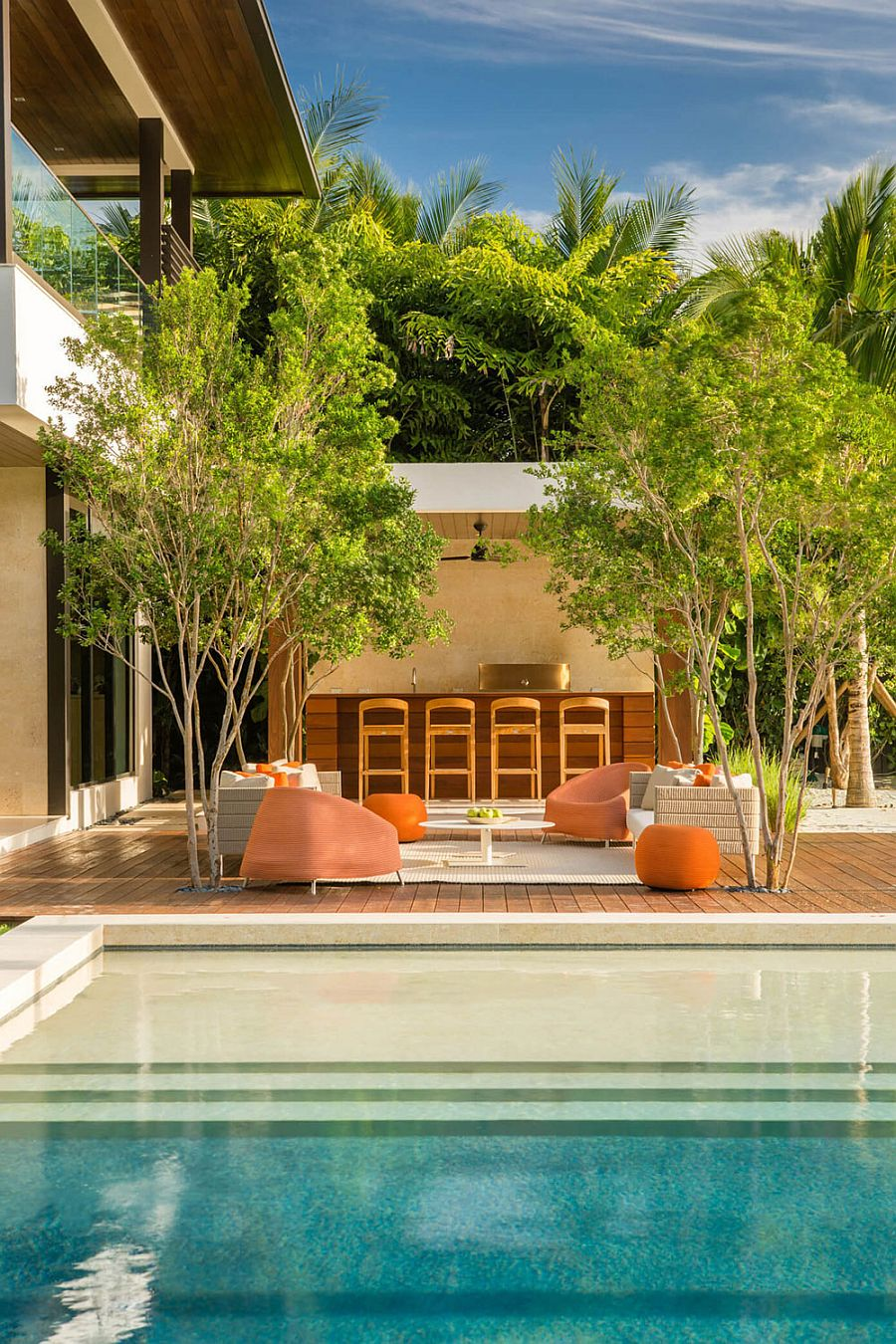 Contemporary outdoor sitting space and pool deck of awesome Miami home