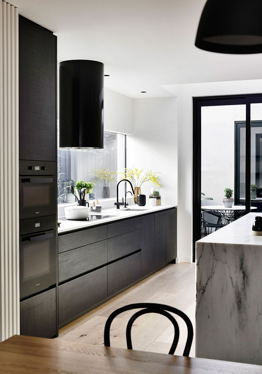 Dark cabinets add contrast to the white kitchen with a gorgeou marble island