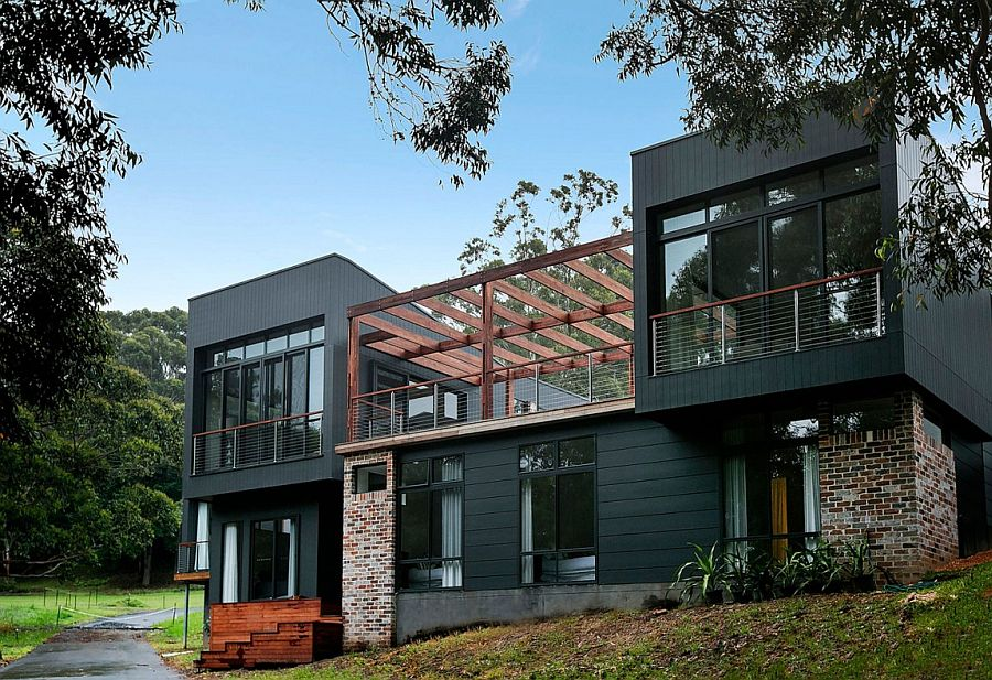 Dark facade and brick walls give the home's facade a unique look