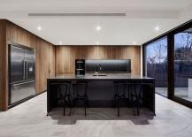 Dark island and fascinating wooden shelves shape a stunning, minimal kitchen