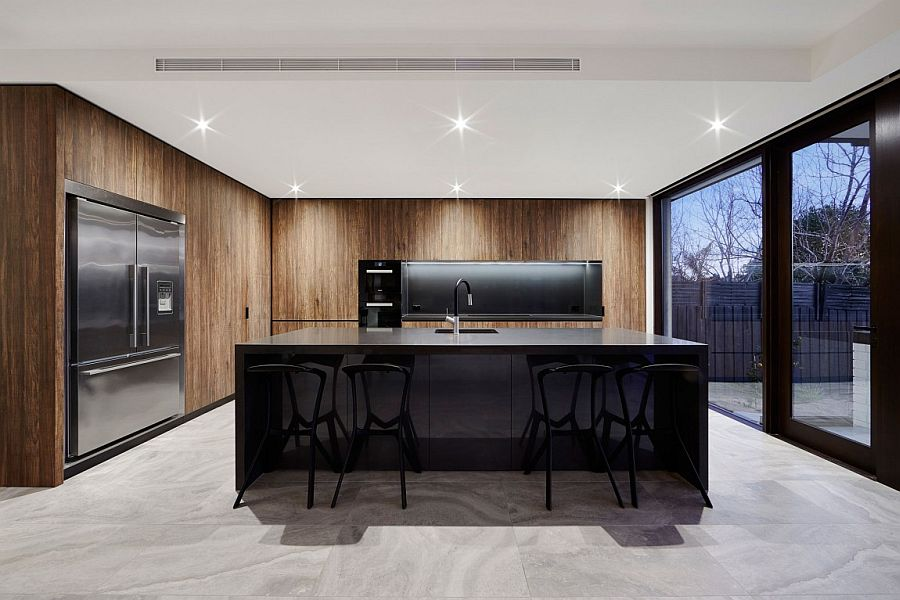 Dark island and fascinating wooden shelves shape a stunning, minimal kitchen