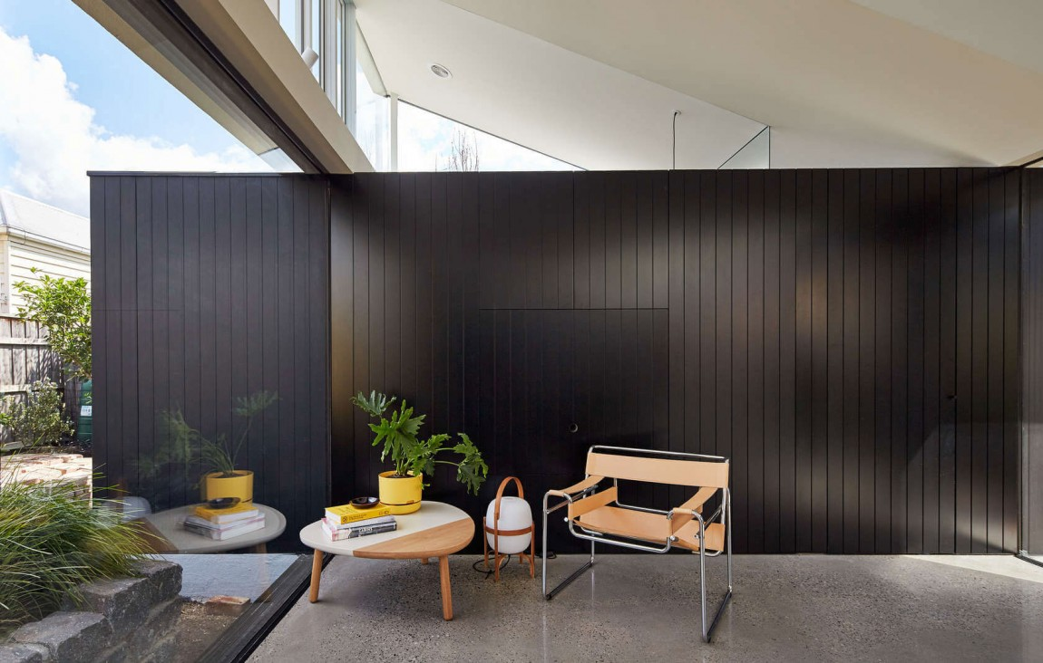 Dark wall adds visual contrast to the open and airy contemporary interior