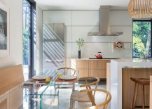 Dining area and kitchen with warm wooden tones and cool decor pieces like the wishbone chair and Seppo Koho pendant