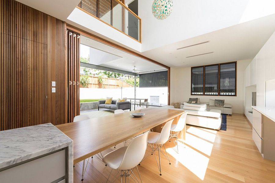 Eight person polished oak dining table next to the kitchen island