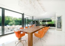 Fabulous dining area with a large wooden dining table and bright orange chairs