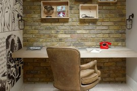 Home office with brick wall, custom wooden shelves and comic strip-styled wall art