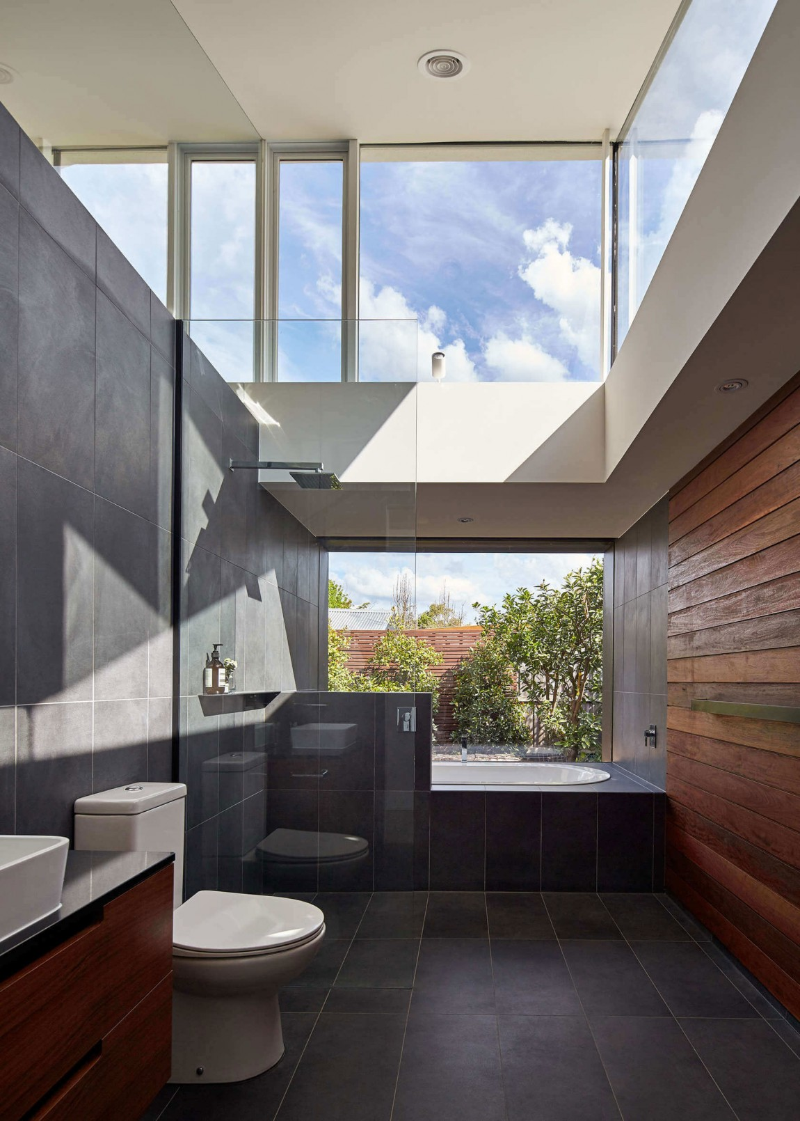 Ingenious bathroom design with accent wood wall and glassy charm