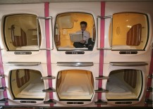 businessman works inside sleeping pod at Japanese capsule hotel