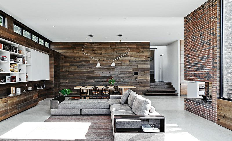 Large living area and dining space with reclaimed wood walls and concrete floor