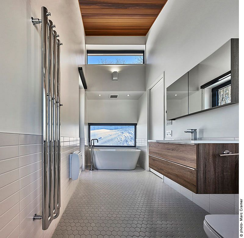 Master bathroom of the ski chalet with hexagonal floor tiles and windows