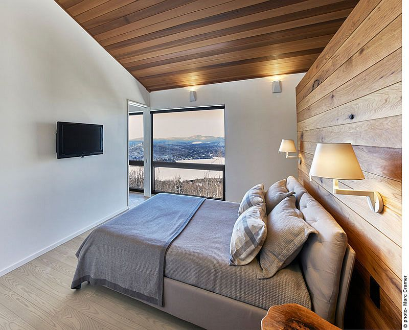 Master bedroom with an accent wooden wall and ceiling