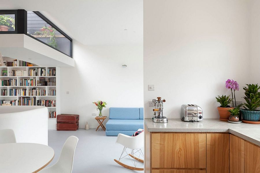 Midcentury classics coupled with large bookshelf and colorful couch in the living room