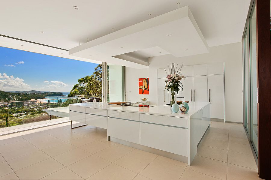 Minimal kitchen in white with a view of the distant coastline [Design: Site Specific Designs]