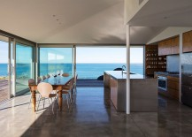 Modern kitchen overlooking the ocean as it flows into the timber deck outside