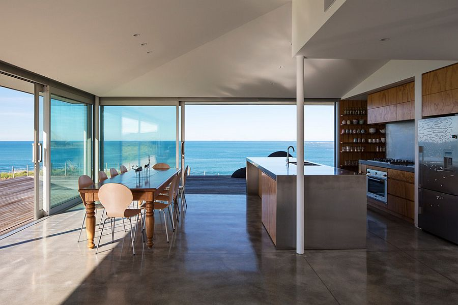 Modern kitchen overlooking the ocean as it flows into the timber deck outside [Design: Julian-Guthrie]