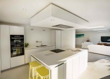 Open design of the new lower level brings sunlight into the contemporary kitchen in white