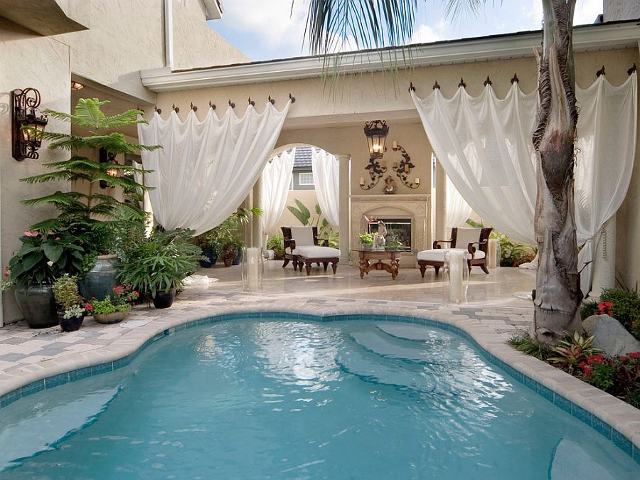 Outdoor drapery adds a hint of visual softness to the pool and its surrounding space