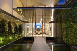 Perfect use of greenery, koi pond and in-ground lighting to fashion a captivating entrance