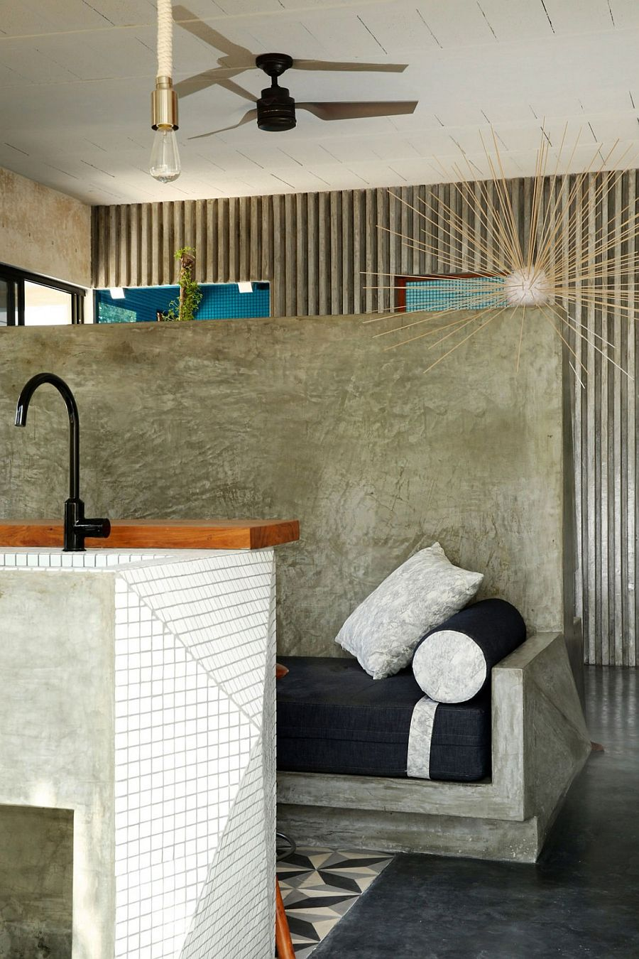 Polsihed cement bench in the kitchen with comfy cusion in dark blue