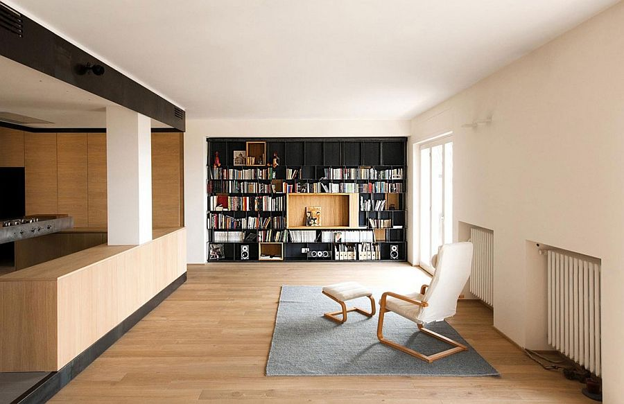 Renovated living room with a dark bookshelf that brings visual contrast 60s Italian Apartment Renovated Using Wood, Iron and Three Large Boxes!