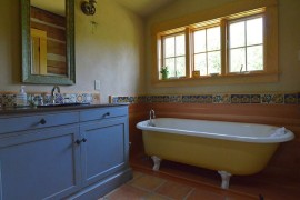 Rustic bathroom with clawfoot bathtub in yellow and vanity in blue