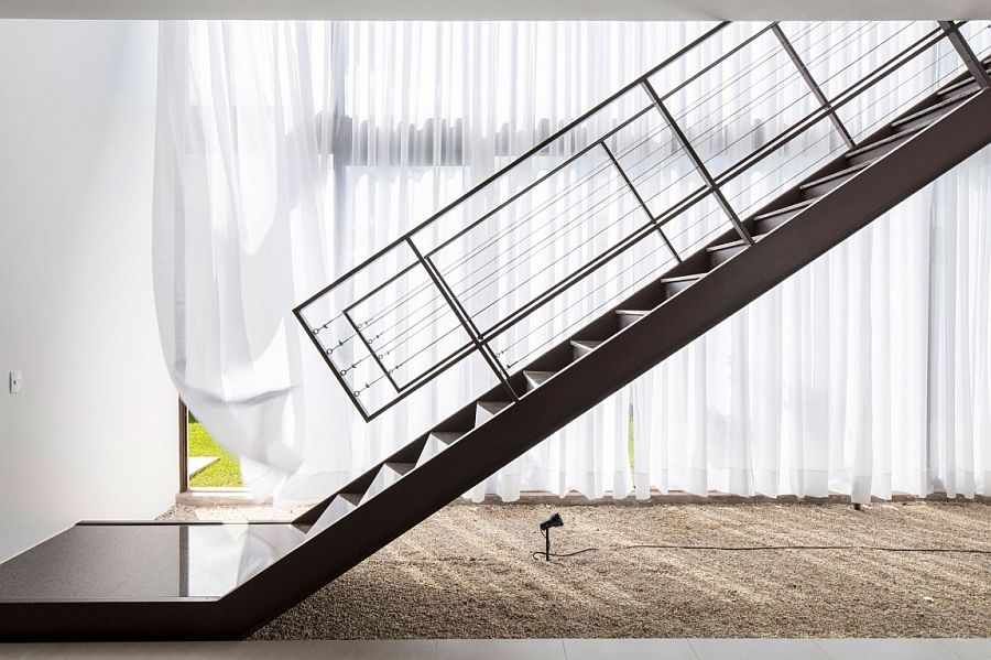Sculptural steel staircase inside contemporary Brazilian home