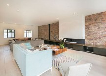 Sleek, modern cabinets and contemporary fireplace combined with exposed brick wall