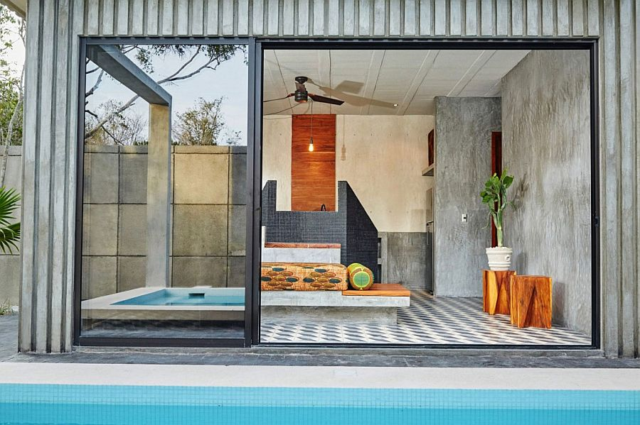 Sliding glass doors connect the indoor social zone with the pool