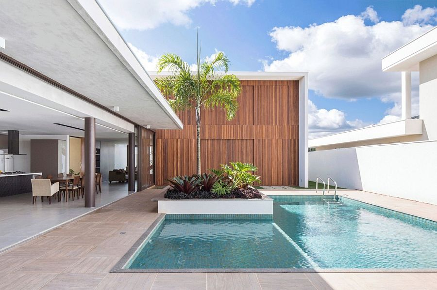 Sliding glass doors connect the lower level living area with the pool space