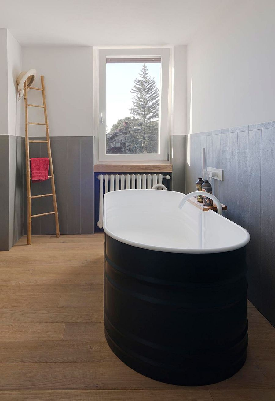 Small bathroom with gray half walls and bathtub in black