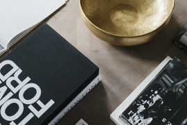 Stacks of books and a gold-toned bowl on a modern coffee table