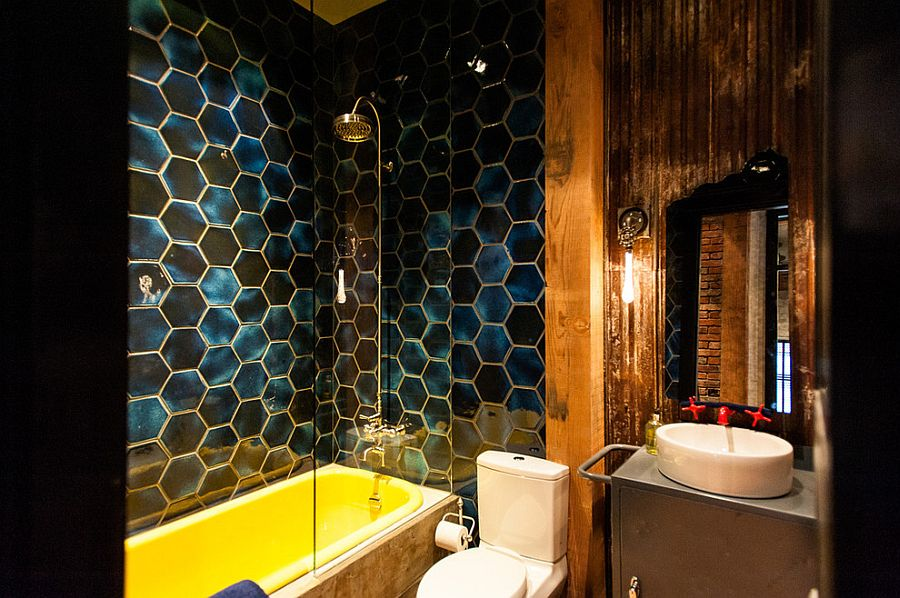 Stunning eclectic industrial bathroom with bold hexagonal tiles and a bathtub in yellow [Design: Beyond Beige Interior Design]