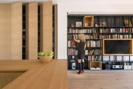 Use of custom wooden boxes adds contrast to the bookshelf in the living room