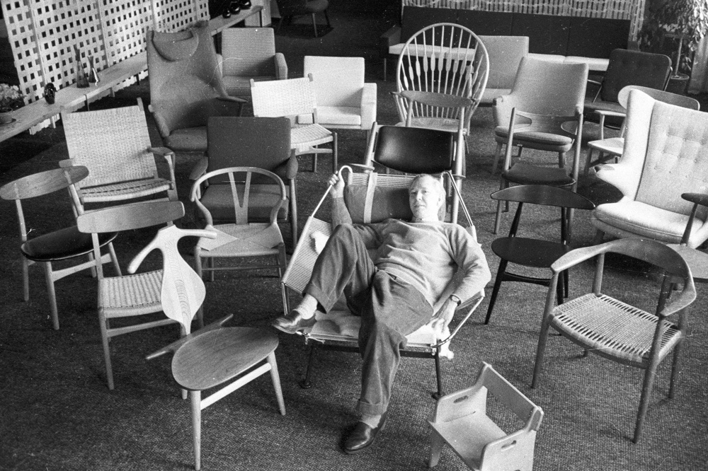 Wegner is pictured lounging on the Flag Halyard Chair, surrounded by his many chair designs. Image via The Line.